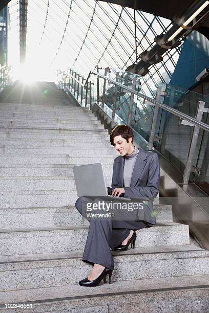 Germany, Bavaria, Munich, Business woman sitting on staircase using laptop