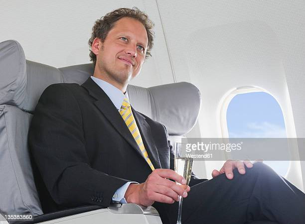 Germany, Bavaria, Munich, Businessman drinking champagne in business class airplane cabin, smiling