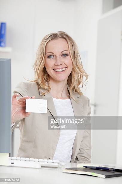 Germany, Bavaria, Munich, Businesswoman holding blank business card in office, smiling