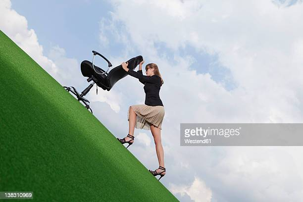 germany, bavaria, munich, businesswoman pushing chair on lawn - torto imagens e fotografias de stock