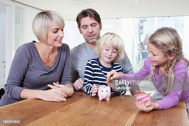 Germany, Bavaria, Munich, Child saving money in piggy bank while parents looking
