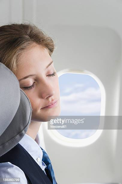 Germany, Bavaria, Munich, Close up of young stewardess sleeping in business class airplane cabin