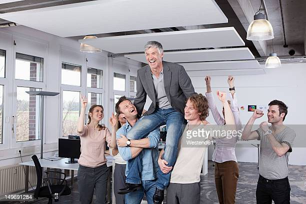 Germany, Bavaria, Munich, Colleagues carrying mature man on shoulder, smiling