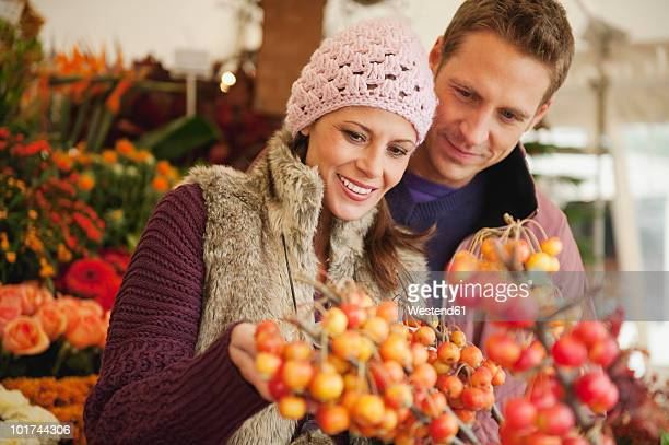 Germany, Bavaria, Munich, Couple at Viktualienmarkt, woman holding berries
