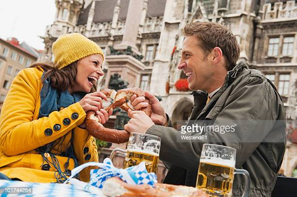 Germany, Bavaria, Munich, Couple holding pretzel, laughing, portrait