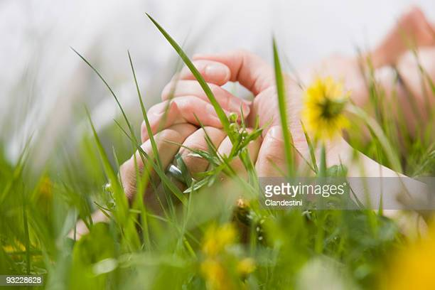 Germany, Bavaria, Munich, Couple lying in meadow, holding hands, close-up