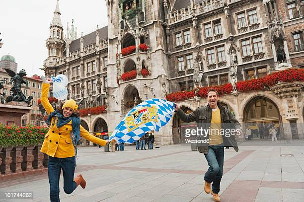 germany, bavaria, munich, couple running over place carrying balloons and bavarian flag, laughing, portrait - marienplatz stock pictures, royalty-free photos & images