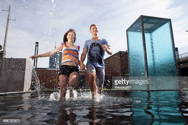 Germany, Bavaria, Munich, Couple running through water at fountain