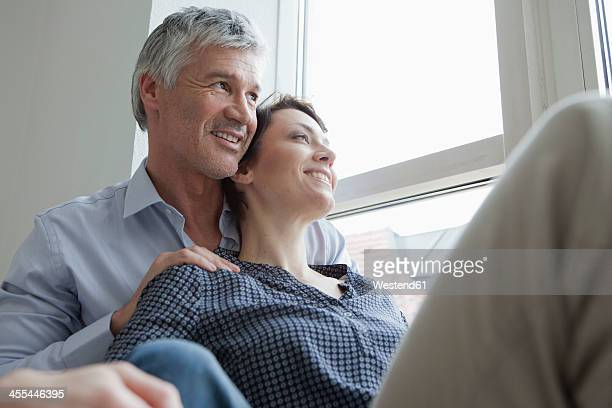 Germany, Bavaria, Munich, Couple sitting at window, smiling