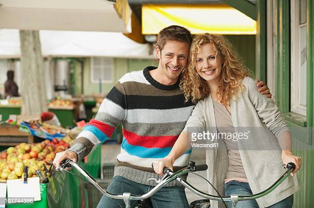 germany, bavaria, munich, couple with bicycles at viktualienmarkt - viktualienmarkt stock pictures, royalty-free photos & images