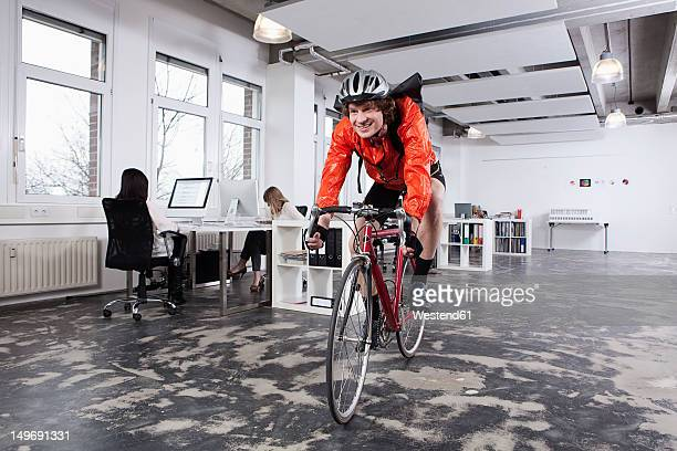Germany, Bavaria, Munich, Courier man cycling in office, colleagues working