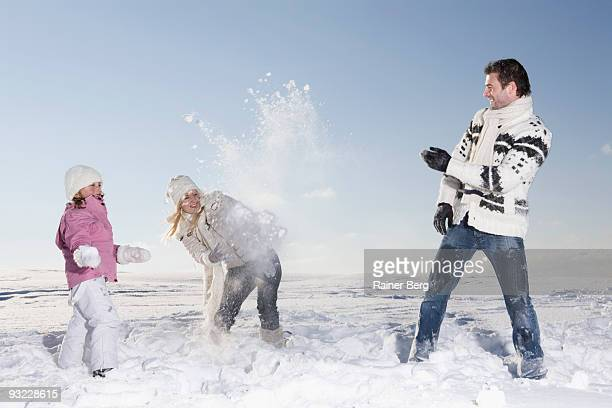 Germany, Bavaria, Munich, Parents with daughter (6-7) having snowball fight