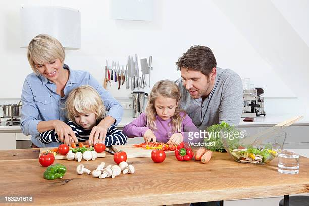Germany, Bavaria, Munich, Family preparing food in kitchen