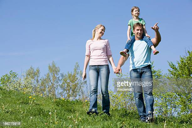 germany, bavaria, munich, family walking in meadow, father carrying daughter (6-7) on shoulders, portrait - upper bavaria stock photos and pictures