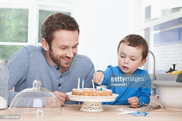 Germany, Bavaria, Munich, Father and son (2-3 Years) preparing birthday cake