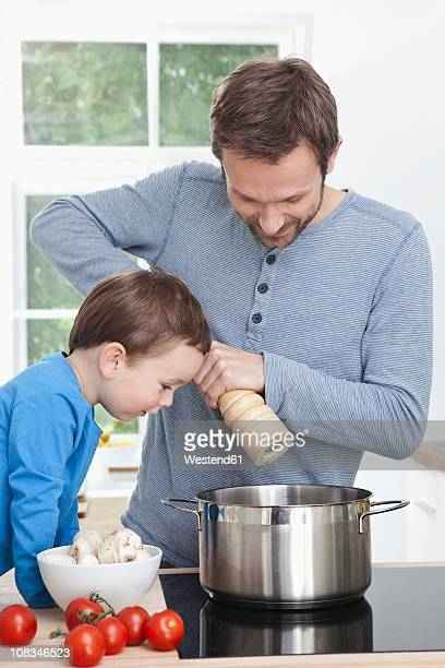 germany, bavaria, munich, father and son (2-3 years) preparing meal in kitchen - 30 34 years fotografías e imágenes de stock
