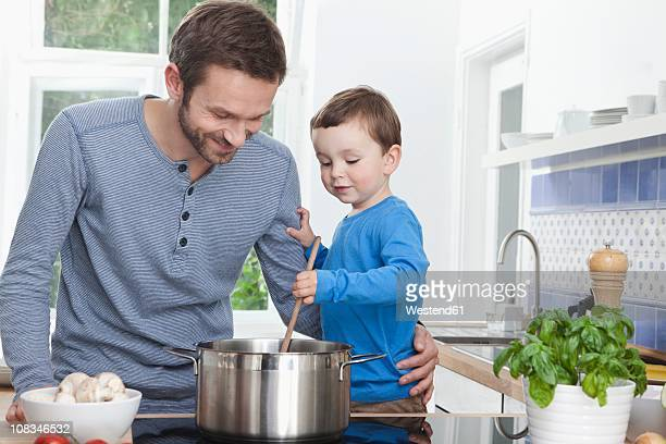Germany, Bavaria, Munich, Father and son (2-3 Years) preparing meal in kitchen