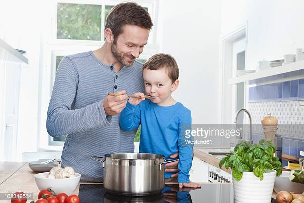 Germany, Bavaria, Munich, Father feeding meal to son (2-3 Years)