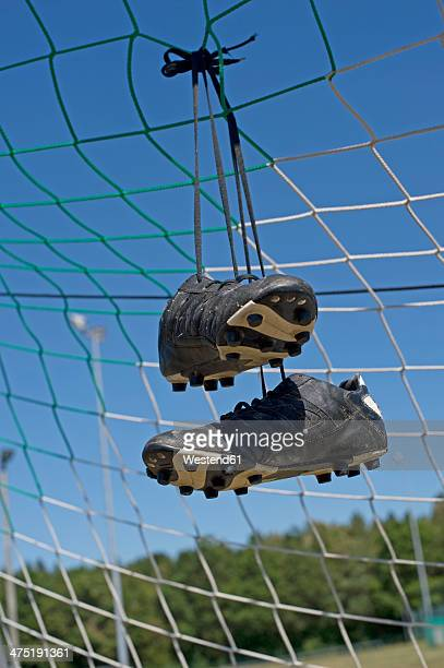 Germany, Bavaria, Munich, football shoes hanging in football net