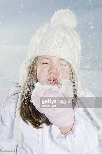 Germany, Bavaria, Munich, Girl (4-5) blowing snow off hand, eyes closed, close-up