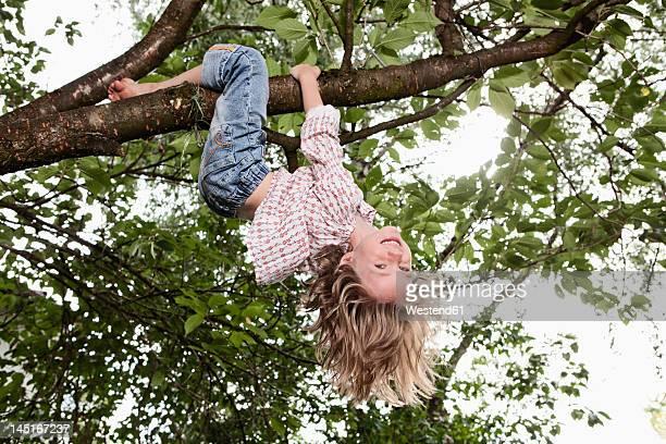 Germany, Bavaria, Munich, Girl hanging on tree, smiling