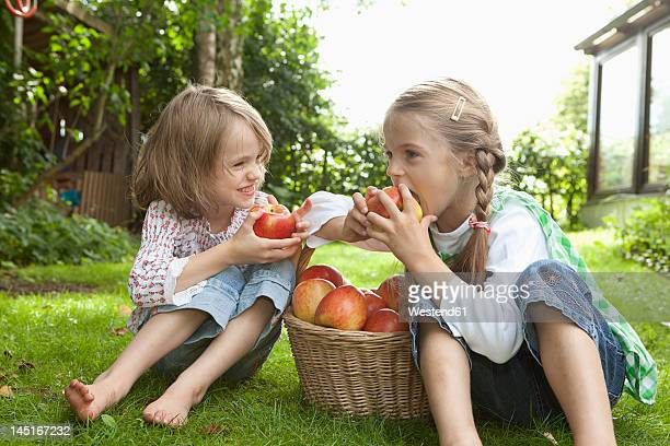 Germany, Bavaria, Munich, Girls eating apple in garden