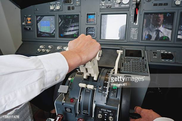 Germany, Bavaria, Munich, Hands of pilot and co-pilot piloting aeroplane from airplane cockpit