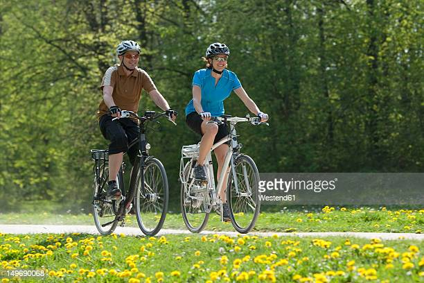 Germany, Bavaria, Munich, Man and woman riding electric bicycle