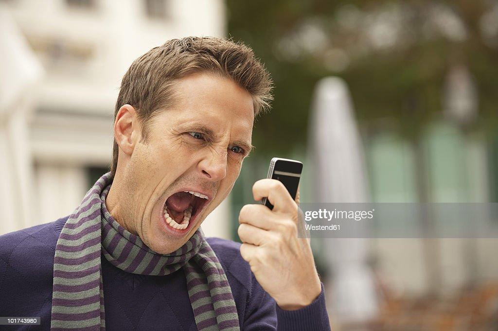Germany, Bavaria, Munich, Man holding mobile phone, screaming, portrait : ストックフォト