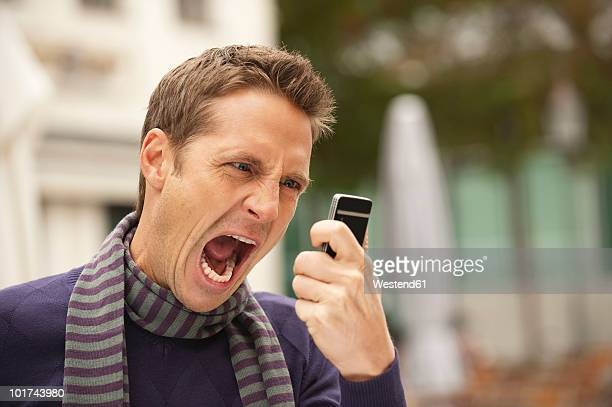 germany, bavaria, munich, man holding mobile phone, screaming, portrait - misnoegd stockfoto's en -beelden