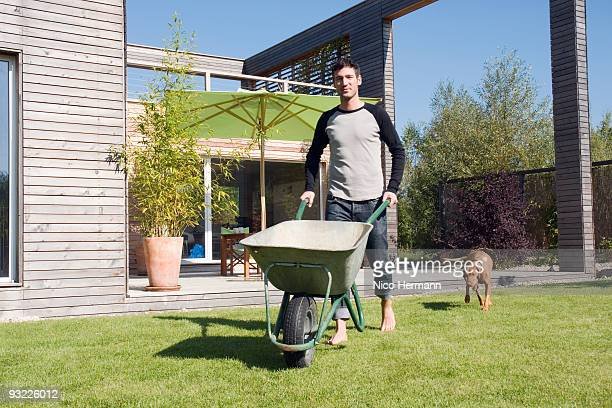 germany, bavaria, munich, man in garden, pushing wheel barrow - wheelbarrow stock photos and pictures