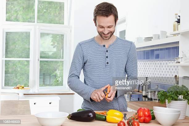 germany, bavaria, munich, man peeling carrot for meal - dunschiller stockfoto's en -beelden