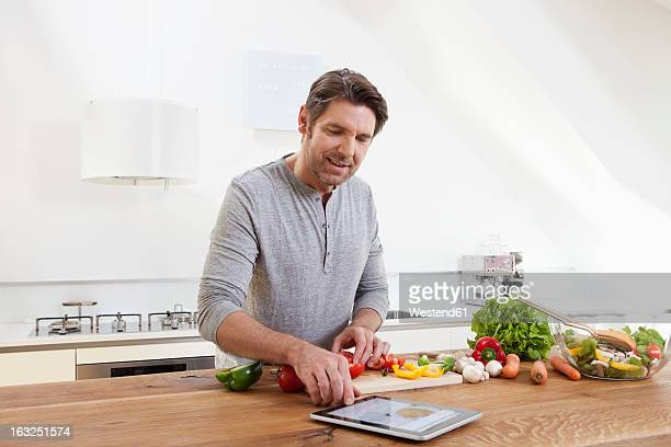Germany, Bavaria, Munich, Man preparing food while looking digital tablet