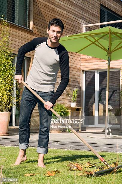 germany, bavaria, munich, man raking leaves in garden, smiling, portrait - sweeping stock pictures, royalty-free photos & images
