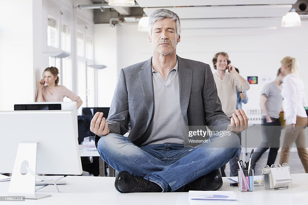 Germany, Bavaria, Munich, Man sitting in lotus position, colleagues in background : Stock Photo