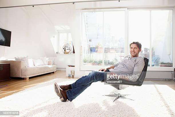 Germany, Bavaria, Munich, Man sitting on chair, smiling