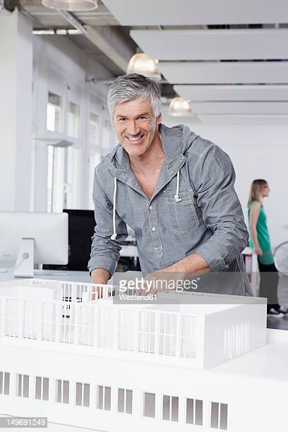 Germany, Bavaria, Munich, Man standing with architectural model in office