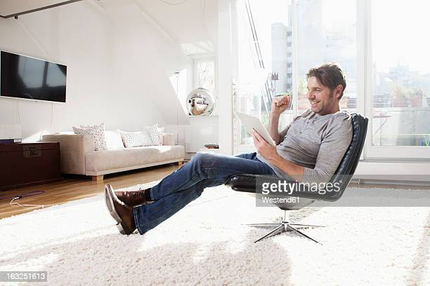 Germany, Bavaria, Munich, Man using digital tablet, smiling