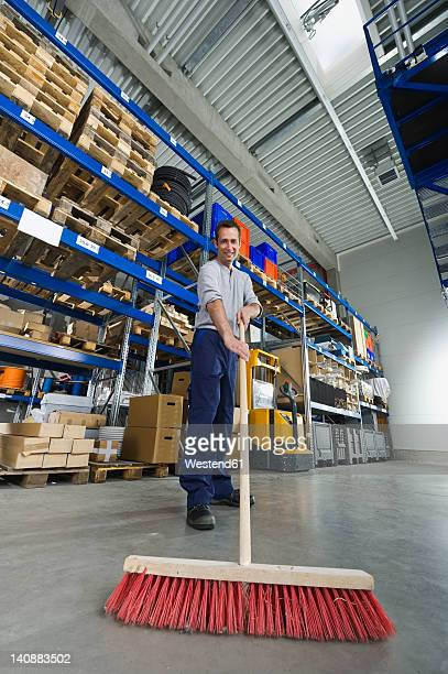 Germany, Bavaria, Munich, Manual worker cleaning warehouse with broom