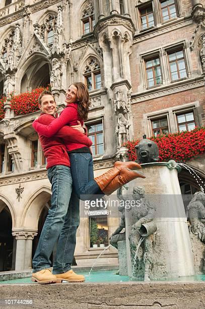 Germany, Bavaria, Munich, Marienplatz, Couple embracing by fountain, portrait