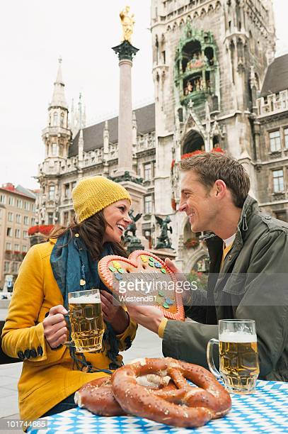 germany, bavaria, munich, marienplatz, couple, man holding gingerbread heart, portrait - new town hall munich stock pictures, royalty-free photos & images