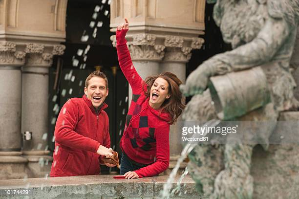 Germany, Bavaria, Munich, Marienplatz, Couple throwing coins into fountain