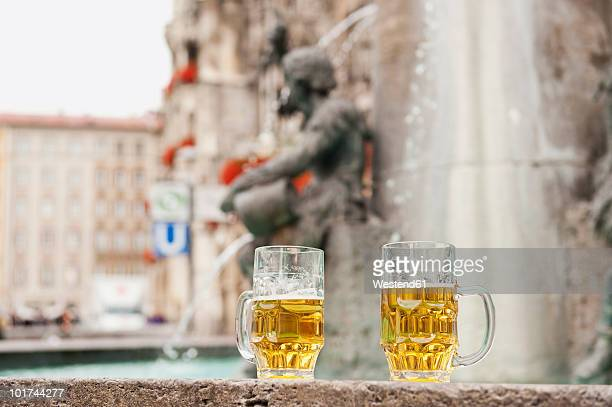 germany, bavaria, munich, marienplatz, two beer mugs standing by fountain - marienplatz stock pictures, royalty-free photos & images
