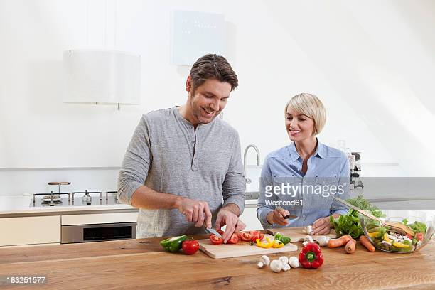 Germany, Bavaria, Munich, Mature couple chopping vegetables in kitchen, smiling