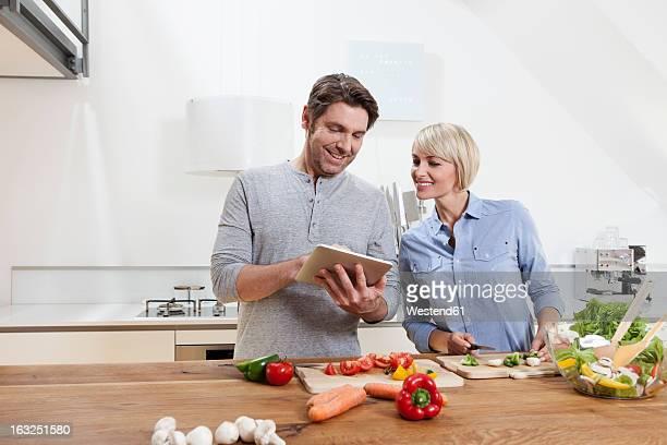Germany, Bavaria, Munich, Mature couple preparing food while looking digital tablet