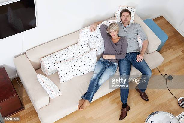 Germany, Bavaria, Munich, Mature couple relaxing on sofa