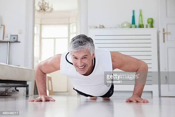 Germany, Bavaria, Munich, Mature man doing push ups at home, smiling