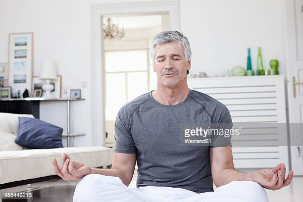 Germany, Bavaria, Munich, Mature man doing yoga at home