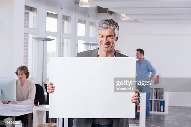 germany, bavaria, munich, mature man holding placard in office - halten stock-fotos und bilder