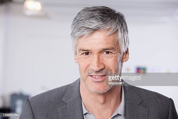 Germany, Bavaria, Munich, Mature man in office, smiling, portrait